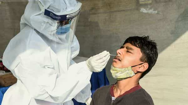A health worker collects a swab sample from to test for Covid-19 (AFP)