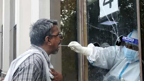 A health worker collects swab samples from a man at the COVID19 testing center (ANI)