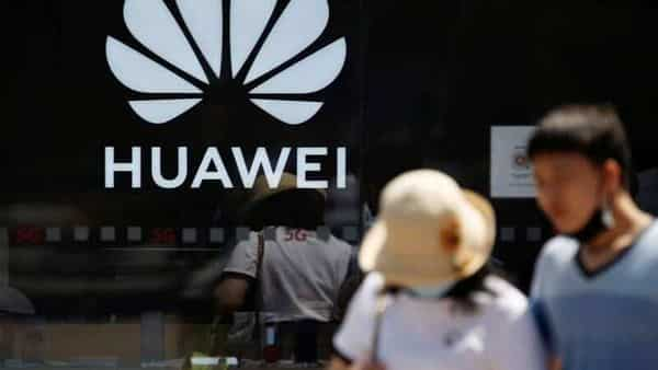 FILE PHOTO: People walk past a Huawei logo on the facade of its store at a shopping complex in Beijing, China (REUTERS)