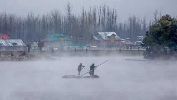Men row their makeshift raft made of plastic pipes on the waters of Dal Lake after a brief spell of fresh snowfall in Srinagar. (AP)