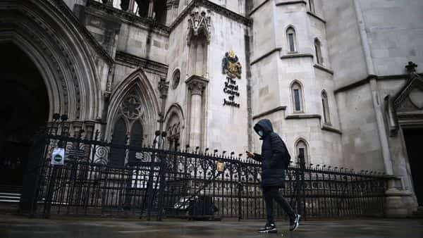 A pedestrian walks past the Royal Courts of Justice, home to the High Court, in London on January 19, 2021. - Meghan Markle's high-profile lawsuit against a British newspaper group for privacy and copyright breaches returns to the High Court in London on January 19, 2021, with the duchess potentially days away from winning the case. Meghan, who with her husband Prince Harry is waging an increasingly public war with some media outlets, is suing the publishers of the Mail on Sunday, Daily Mail and MailOnline. (Photo by DANIEL LEAL-OLIVAS / AFP) (AFP)