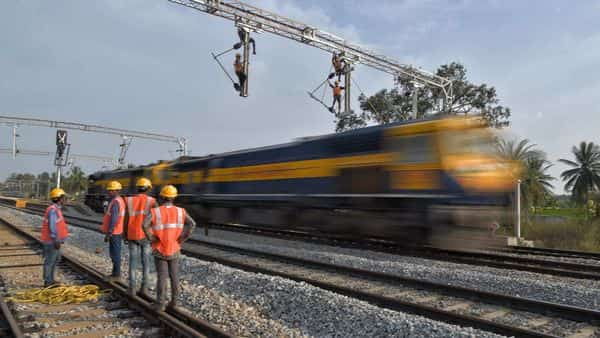 Workers on contract for Indian Railways, erect infrastructure for drawing electric cable lines over railway tracks for use by locomotives on the outskirts of Bangalore on January 15, 2021. (Photo by Manjunath Kiran / AFP) (AFP)