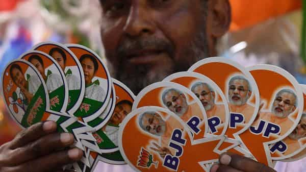 A shopkeeper displays campaigning material of political parties (AFP)