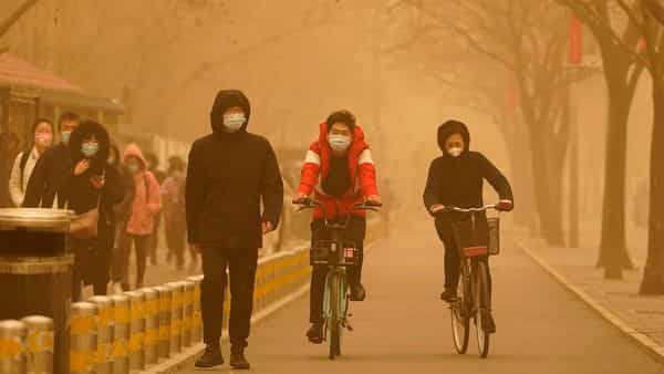 Residents make their way through a sandstorm in Beijing, Monday, March 15, 2021. The sandstorm brought a tinted haze to Beijing's skies and sent air quality indices soaring on Monday. (AP Photo/Ng Han Guan) (AP)