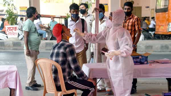 A medic collects a swab sample of man for the COVID-19 test amid the rise in cases, in New Delhi. (ANI)