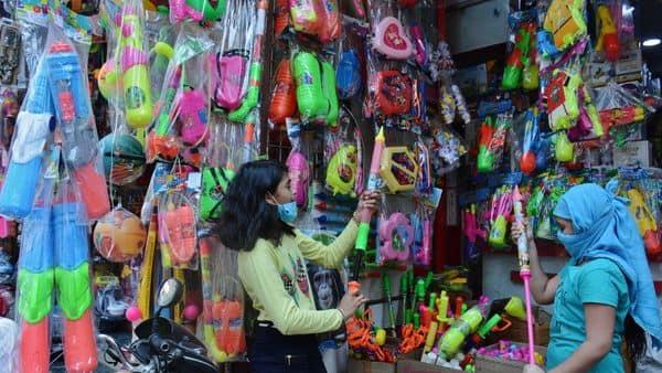 A girl browses through spray guns ahead of the Holi festival.
