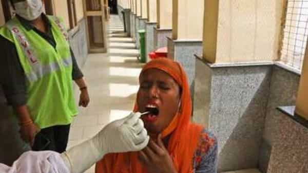 A health worker collects swab to test for COVID- 19 at a government hospital (AP)