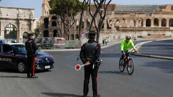 A cyclist rides past Carabinieri police officers at road block near the Colosseum, in downtown Rome (AP)