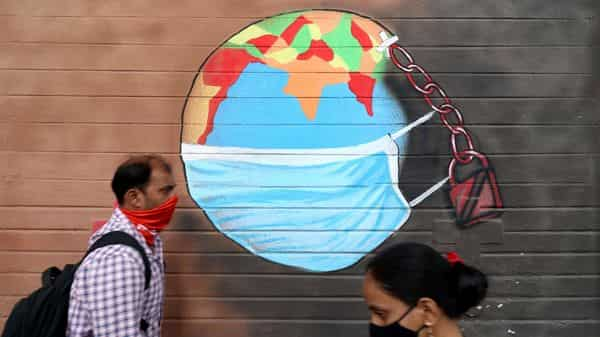 A man and a woman wearing protective face masks walk past a graffiti on a wall, amidst the spread of the coronavirus disease (COVID-19), in Mumbai, India (REUTERS)