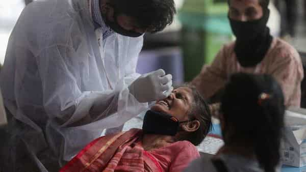 A health worker collects nasal swab of a passenger for COVID-19 test at a long-distance train station in Mumbai, (AP)