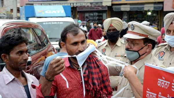 Police personnel distribute mask during an awareness campaign against the spread of the coronavirus, in Amritsar. (PTI)