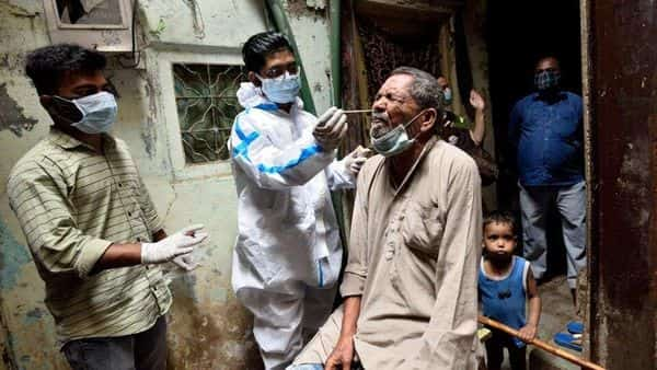 A BMC healthcare worker collects swab samples of Dharavi residents. (Satish Bate/HT Photo) (HT_PRINT)