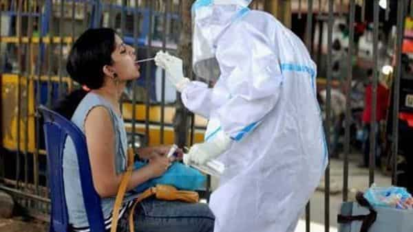 A health worker wearing a PPE kit collects a sample from a woman for the Covid-19 Rapid Antigen Test in Bengaluru. (PTI)