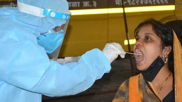 A medic takes a swab sample from a woman for COVID-19 test (PTI)