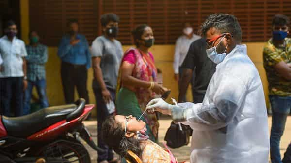 A health worker collects a swab sample from a young woman for COVID-19 test, in Mumbai, Wednesday (PTI)