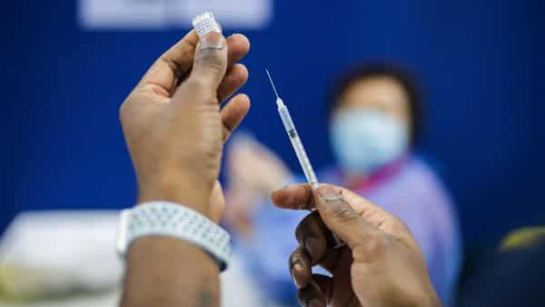A healthcare worker prepares an intravenous dose of a Covid-19 vaccine, produced by Pfizer and BioNTech SE, at a Covid-19 vaccination centre. (Bloomberg)