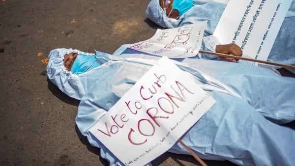 Protesters wearing protective suits and masks display placards laying on the street near the Election Commission office in Kolkata  (AFP)