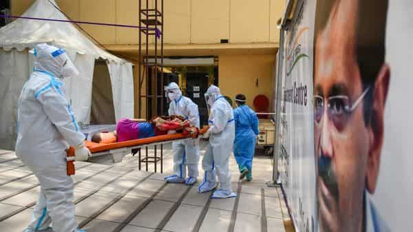 Health workers in PPE shifting a Covid-19 patient to an isolation ward at the temporary Covid Care facility at Shehnai Banquet in New Delhi.