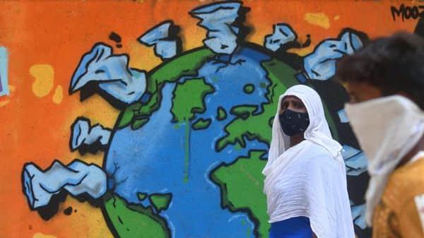 Mumbai, India - April 17, 2021: A womwen passing near the COVID-19 graffiti wall at Bandra in Mumbai, India, on Saturday, April 17, 2021.  (Photo by Satish Bate/Hindustan Times) (Satish Bate/HT Photo)