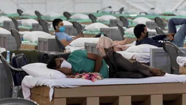 Patients rest laying on beds made out of cardboard inside the campus hall of spiritual organisation Radha Soami Satsang Beas (RSSB), converted into a COVID-19 coronavirus care centre (AFP)