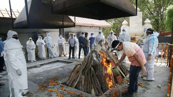 Workers and relatives, wearing PPE kit, performs cremation of a person who died of Covid at the Nigambodh Ghat cremation, amid rise in Covid -19 cases across the country, in New Delhi. (PTI)
