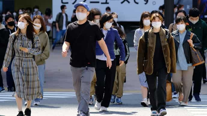 Pedestrians wearing face masks walk over the landmark Shibuya Crossing in the area's shopping and entertainment district in Tokyo, Japan on April 18, 2021.