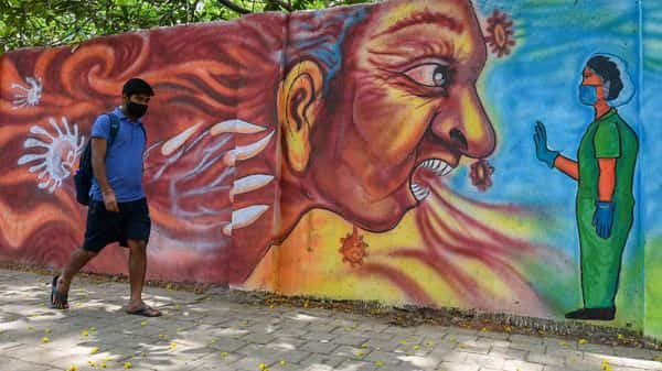 A pedestrian walks past a mural depicting a health worker stopping the Covid-19 in Mumbai. (AFP)