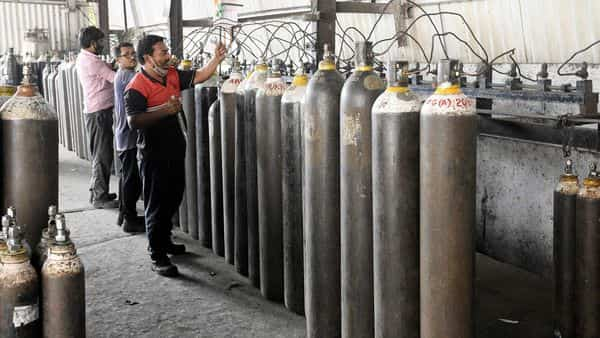 Workers check the oxygen cylinders that will be used to distribute to various hospitals for COVID-19 patients amid the rise in Coronavirus cases, in Surat on Thursday. (ANI Photo)