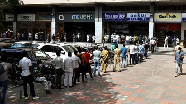 People stand in a long queue to buy liquor outside a liquor shop in Khan Market. (ANI)