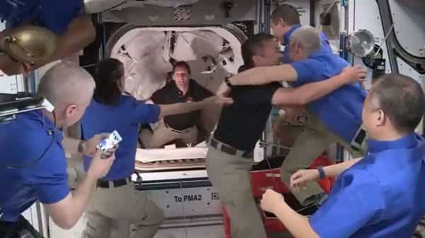 TOPSHOT - This screen grab taken from the NASA live feed shows crew members of the International Space Station welcoming crew members of the SpaceX's Crew Dragon spacecraft after docking an opening hatches, on April 24. (AFP)