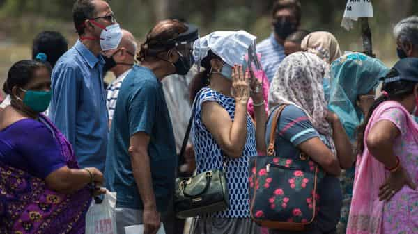 People stand in a queue in the hot weather for Covid-19 vaccination at NESCO Vaccination Centre, Goregaon in Mumbai.