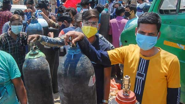 Family members of COVID-19 patients wait to fill their empty cylinders with medical oxygen outside an oxygen filling center. (PTi)