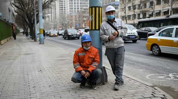 Chinese workers outside a construction site in Beijing. (AFP)