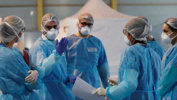 Medical staff, wearing protective suits and face masks. (Reuters)