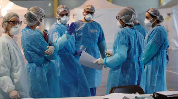 Medical staff, wearing protective suits and face masks, prepare material for medical consultations at an emergency COVID-19 center. (Reuters)