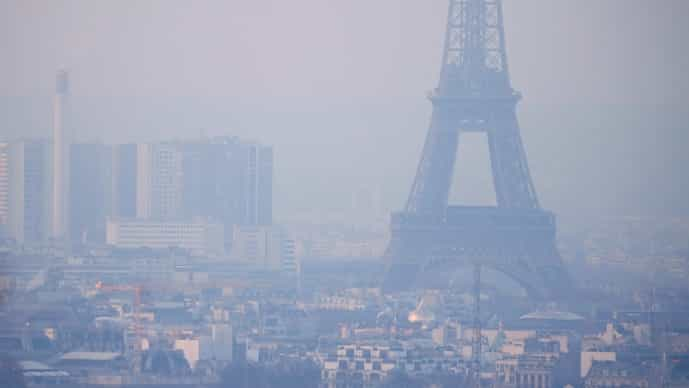 A file photo from 2016 shows the Eiffel Tower surrounded by a small-particle haze which hangs above the skyline in Paris, France,