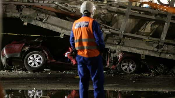 A rescue worker stands in front of a car trapped under an overpass for a metro that partially collapsed with train cars on it at Olivos station in Mexico City. (REUTERS)