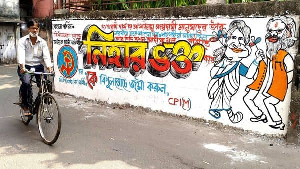 File Photo: A man rides a cycle as he passes by CPIM graffiti ahead of the State Assembly election, at Behala in Kolkata. (ANI)