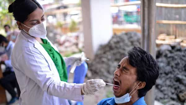 A Bangladeshi health worker takes a mouth swab sample of a man to test for COVID-19 in Dhaka, Bangladesh. (AP)