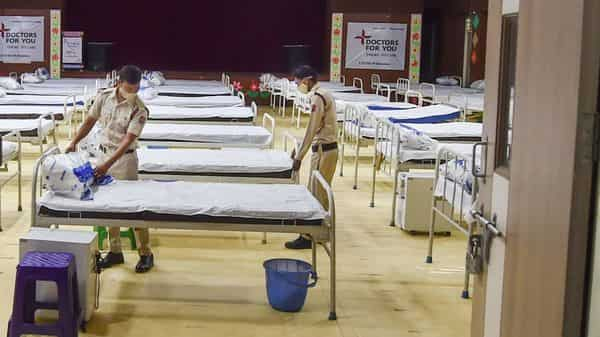 Volunteers prepare beds with oxygen concentrators and oxygen cylinders at a Covid Care Centre. Representational image.  (PTI)
