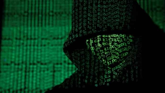 A projection of cyber code on a hooded man is pictured in this illustration. The U.K.'s National Cyber Security Centre took down 700,595 malicious campaigns last year, 15-times more than a year earlier as the number of scams increased.