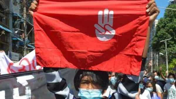 An anti-coup protester holds a slogan bearing the three-finger salute during a demonstration in Yangon, Myanmar on Tuesday  (AP)