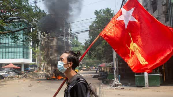 A man holds a National League for Democracy (NLD) flag during a protest against the military coup (REUTERS)