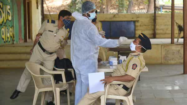 A BMC health worker collects swab samples of police personnel  (HT PHOTO)