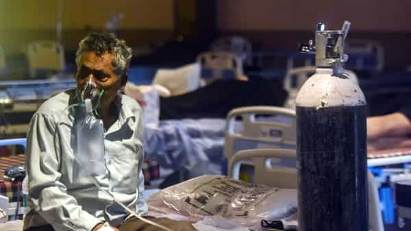 May 14, 2021: A Covid-19 patient wearing an oxygen mask inside a Covid-19 care center set up at Shehnai Banquet, LNJP in New Delhi, India (Amal KS/HT PHOTO)