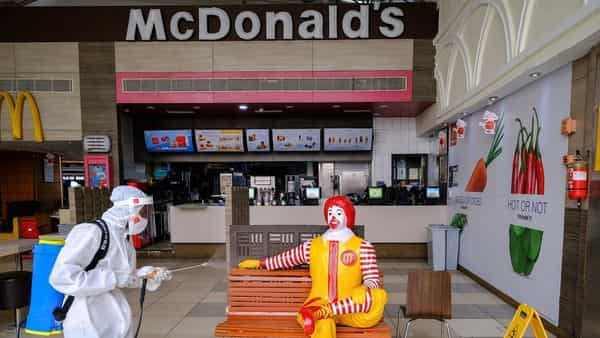 A worker wearing Personal Protective Equipment (PPE) sanitizes a bench and novelty Ronald McDonald figure outside a McDonald's Corp. restaurant at the Ambience Mall in New Delhi,  (Bloomberg)