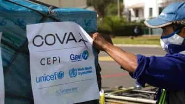 Airport workers spray the cargo of Covax COVID-19 vaccines (AP)