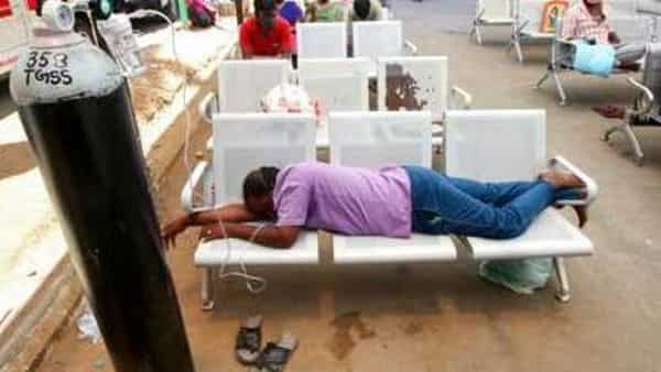A Covid-19 patient on oxygen support waiting for admission lies on chairs outside the Tamil Nadu Government Multi Super Speciality Hospital in Chennai. (AP)