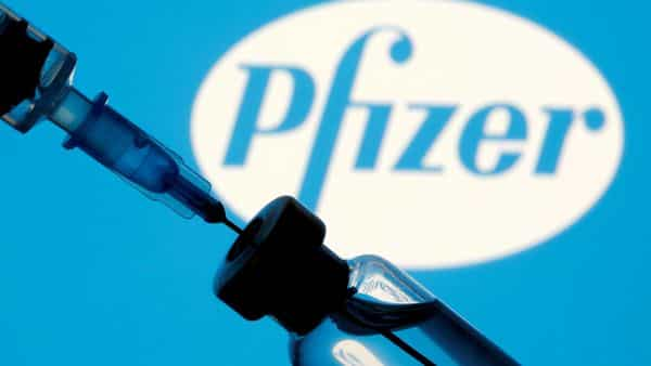 FILE PHOTO: A vial and sryinge are seen in front of a displayed Pfizer logo in this illustration. (REUTERS)