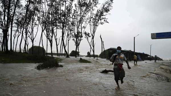 Cyclone Yaas: Residents walk in a beachfront area as seawater reaches a nearby road. (AFP)
